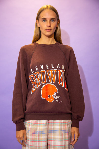 the model wears a brown sweater with cleveland browns spell out on the front