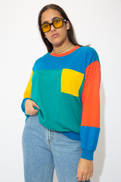 Crewneck style sweater in red, blue, green and yellow. Finished off with shoulder pads, pair with mid-wash jeans and Jordans for a sick fit!