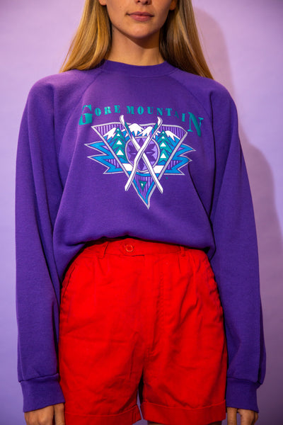 the model wears a purple sweater with a gore mountain spell out on the front