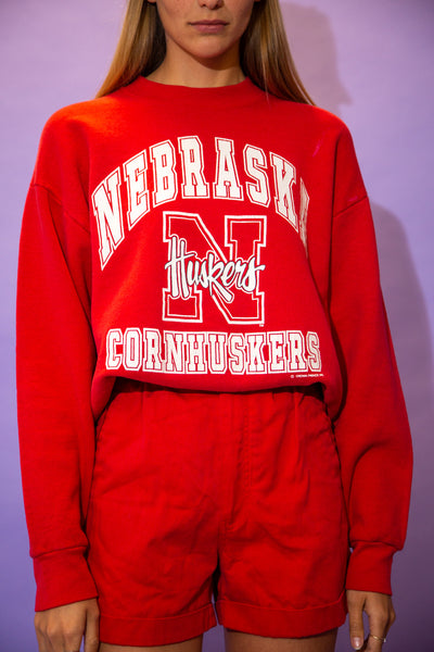 the model wears a red sweater with a nebraska cornhuskers spell out graphic on the front
