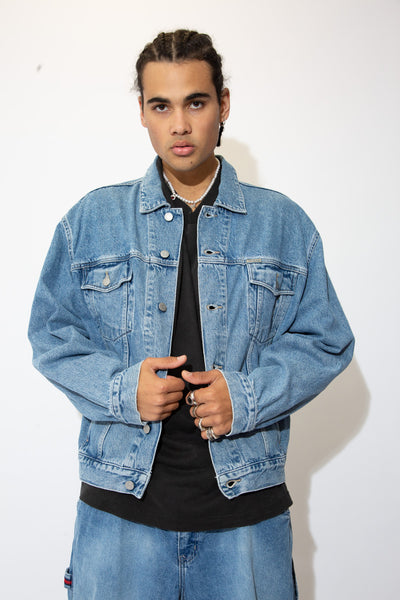 Mid-wash blue denim jacket with grey stitching, double breast pockets, double side pockets and Guess branding on the buttons and left chest pocket.