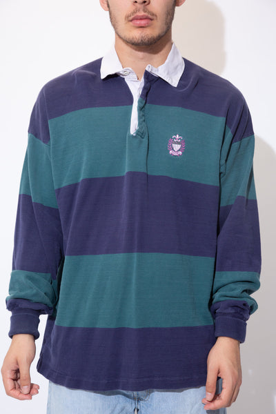 the model wears a navy and teal horizontal striped rugby