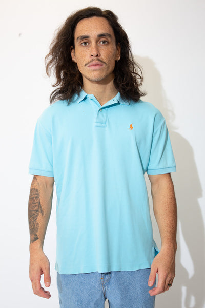 Light blue polo style shirt with white buttons and an orange embroidered Ralph Lauren logo on the left chest.