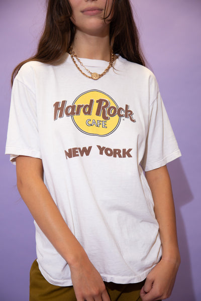 White in colour, this single stitch tee has a yellow and maroon Hard Rock Cafe logo on the front, repping New York below.