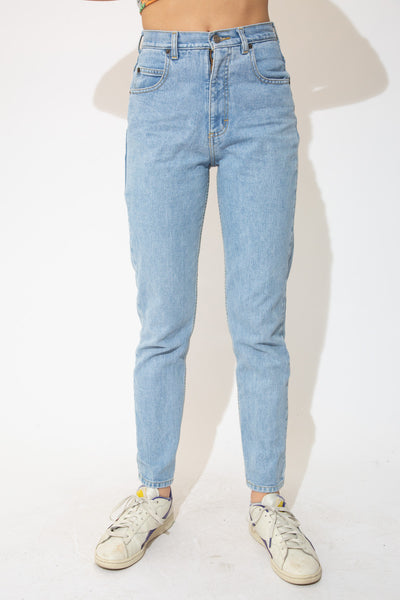 the model wears a light blue wash pair of mom jeans