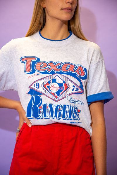 the model wears a grey tee with a texas rangers spell out on the front
