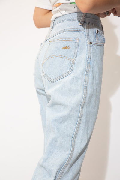 Light wash denim jeans in a straight to tapered leg fit with brown stitching, belt loops, pockets and Chic branding on the button, domes, front pocket and back pocket.