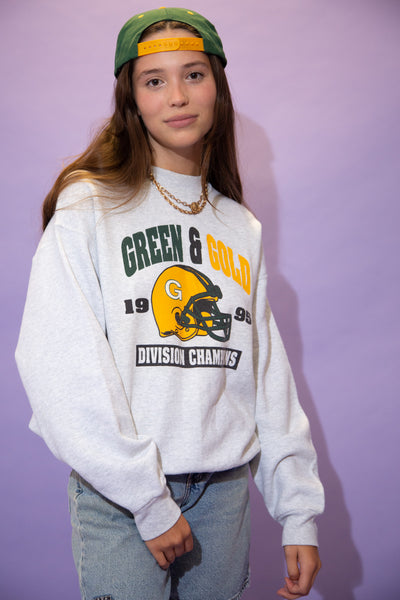 Grey in colour, this jumper has a 'Green and Gold' spell-out across the top, a green and yellow football helmet and the date 1995.