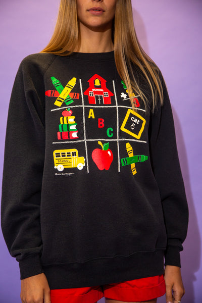 the model wears a faded black sweater with a school graphic on the front