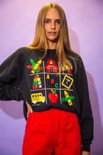 Load image into Gallery viewer, the model wears a faded black sweater with a school graphic on the front