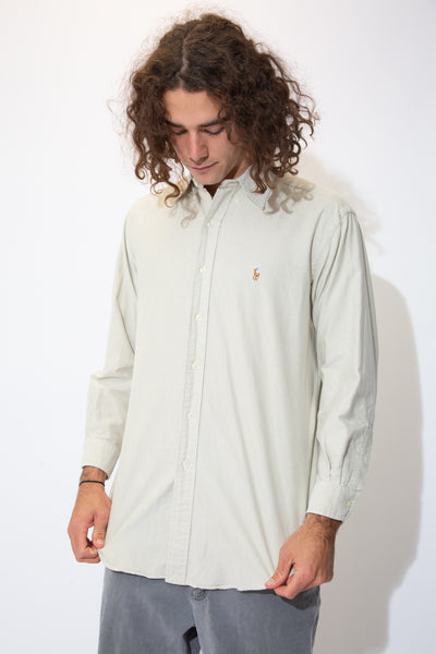 Cream coloured button-up shirt with full-length white buttons and a colour Ralph Lauren logo on the left chest. Pair over a white tee with light wash jeans and Airforce 1s for a laidback fit!