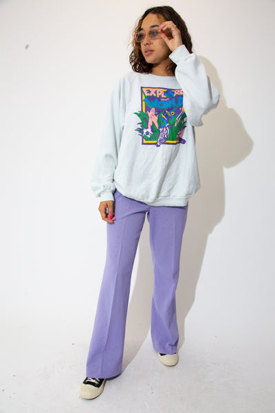 the model wears a blue sweater with 'explore your world' spell out on the front