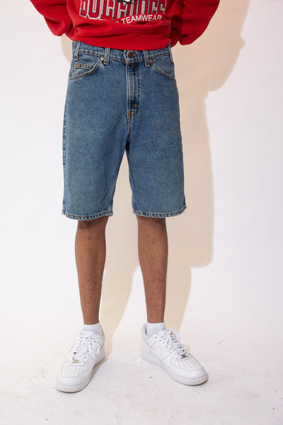 Mid-wash blue denim shorts in a midi-length fit with light brown stitching and Levi's branding on the button, domes, back waistline and back right pocket.