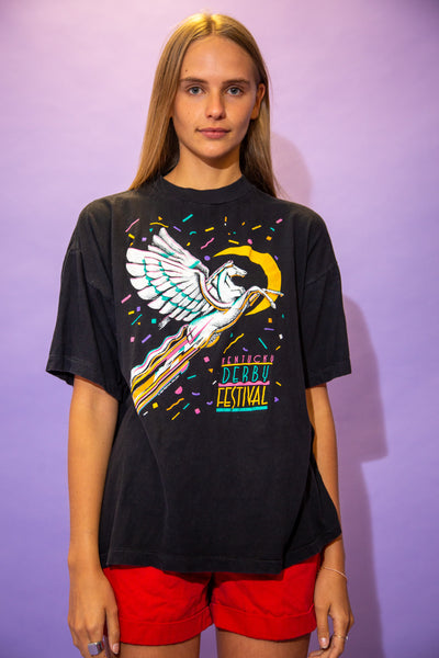 the model wears a faded black tee with a pegasus graphic on the front