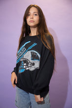 Load image into Gallery viewer,  Black in colour, this jumper has a blue and silver plaque print repping the 'Carolina Panthers' on the front with a large logoed hemet below it.