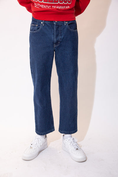 Dark-wash blue jeans in a short straight leg fit with white stitching and Calvin Klein branding on the buttons, front pocket and back waistline.
