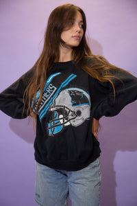 Black in colour, this jumper has a blue and silver plaque print repping the 'Carolina Panthers' on the front with a large logoed hemet below it.