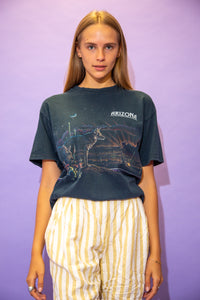 the model wears a black tee with an arizona graphic on the front