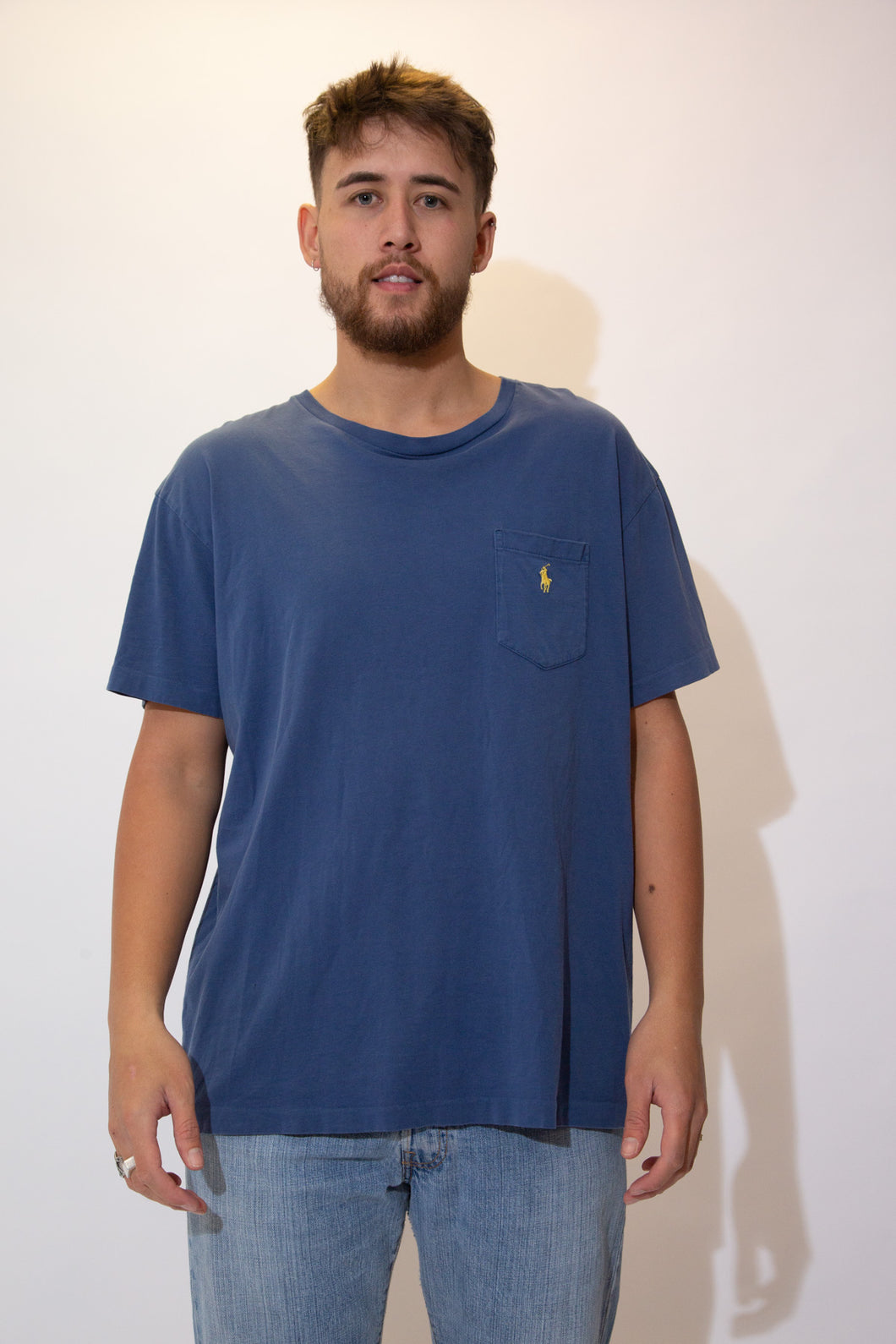 Blue single stitch tee with a yellow Ralph Lauren logo on the left chest pocket. Pair with a dark wash jeans and Jordans for a chill fit!