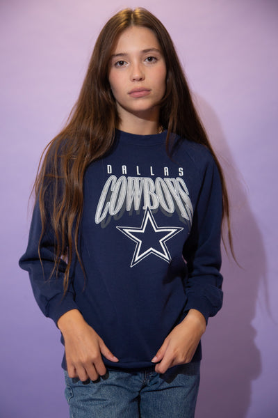 Navy blue sweater with a white and silver 'Dallas Cowboys' spell-out across the front with the teams logo below. Dated 1995