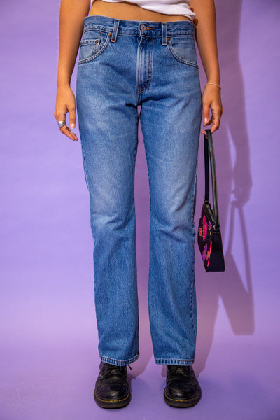 the model wears a pair of mid blue wash levis bootleg