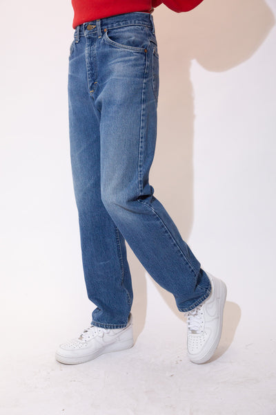 Mid-wash blue jeans in a straight leg fit with light brown stitching and Lee branding on the button, domes, back waistline and back pocket.