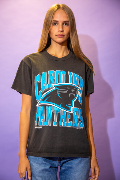 the model wears a faded black tee with a carolina panthers graphic