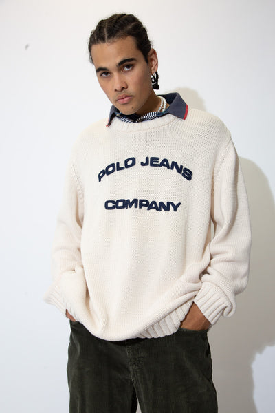 White in colour, this knitted crew neck has a navy blue 'Polo Jeans Company' appliqué on the front.