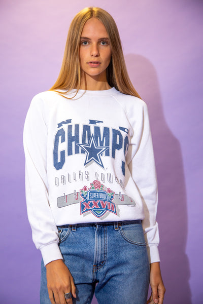 the model wears a white sweater with a dallas cowboys graphic