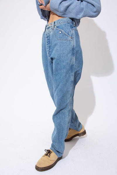 Mid-wash blue jeans in a baggy fit with light brown stitching, shiny white circles on the pockets and Silver Lake branding on the button, domes and back waistline.