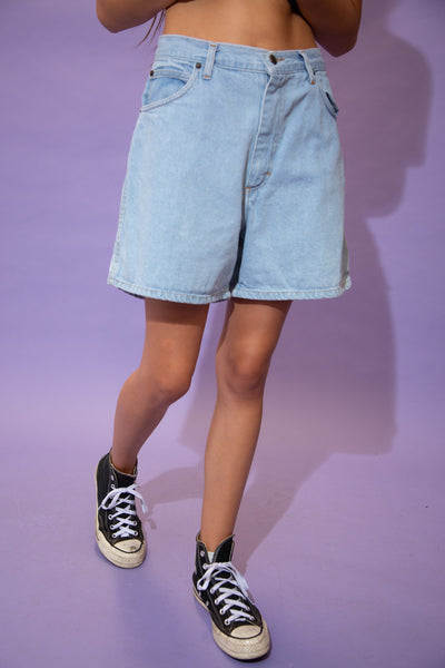 Light wash blue, these denim shorts are in a high waisted style with a midi-length fit, light brown stitching and branding on the button and domes.