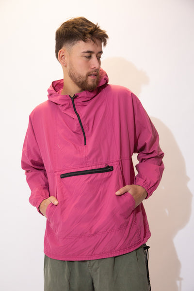 Pink anorak pullover in a quarter zip style with a zip-up kangaroo-pouch style pocket, an adjustable waistline and a hood. Pink anorak pullover in a quarter zip style with a zip-up kangaroo-pouch style pocket, an adjustable waistline and a hood.