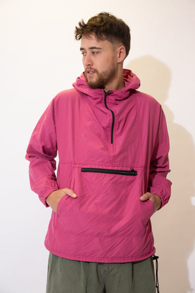 Pink anorak pullover in a quarter zip style with a zip-up kangaroo-pouch style pocket, an adjustable waistline and a hood.