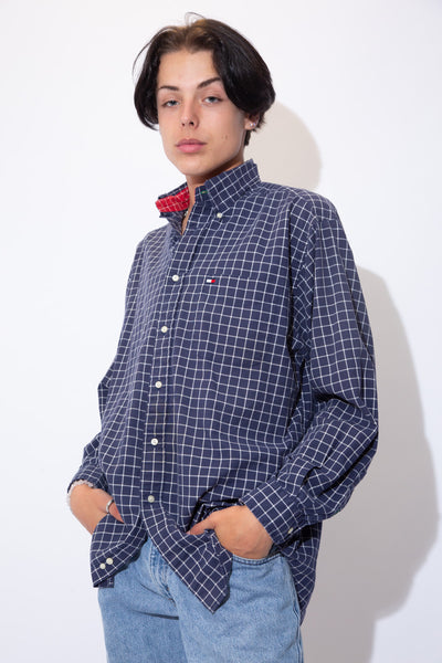 Navy blue button-up with a white checkered detail across the shirt, white buttons and the Tommy Hilfiger logo on the left chest pocket.