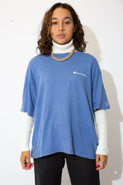 the model wears a pale blue oversized champion tee