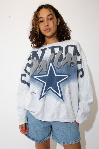 the model wears a grey tee with dallas cowboys spell out