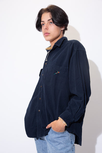 Hop into this naughty Nautica Button-Up now! Thick navy blue button-up with brown full-length buttons and a lil Parrot embroidered on the left chest pocket.
