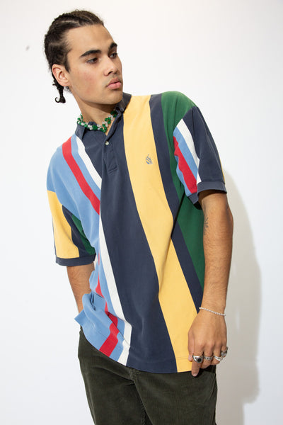 Vertically striped in blues, green, red, yellow and white with white buttons and navy blue Nautica branding on the left chest