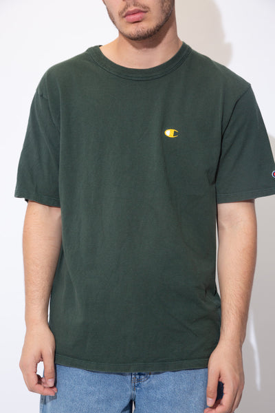 the model wears a khaki green tee with a champion logo on the left breast and arm
