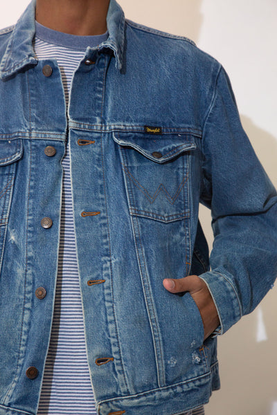 Mid-wash blue denim jacket with brown stitching and Wrangler branding on the left chest pocket and buttons.