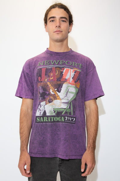 Purple tee with a sick print of a man playing a saxophone on the front. 'Newport Jazz' is printed above with 'Saratoga 1997' printed below.