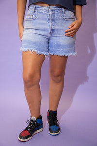 the model wears a pair of light blue washed guess denim shorts