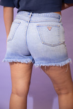 Load image into Gallery viewer, the model wears a pair of light blue washed guess denim shorts