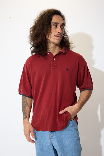 Get naughty in this Nautica Polo! Maroon in colour, this tee has a navy blue striped collar and sleeves with a navy blue Nautica logo on the left chest.