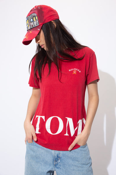 Red in colour, this single stitch tee has a small Hilfiger spell-out on the left chest with the emblem below. A larger Tommy spell-out  wraps around the bottom of the tee with the brand's logo.