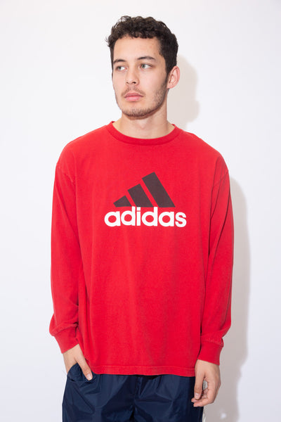 the model wears a red long sleeve with an adidas graphic on the front