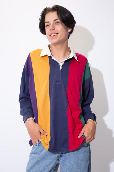 Vertically striped in red, navy blue, yellow, purple and green, this rugby style sweater has a white collar with matching white buttons on the neckline.