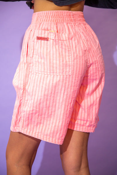 the model wears a pair of pink striped cotton shorts