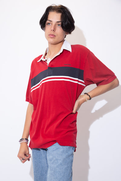 Red rugby style tee with a blue and white striped detail across the chest. With a white collar, matching white buttons and Nautica branding on the left chest