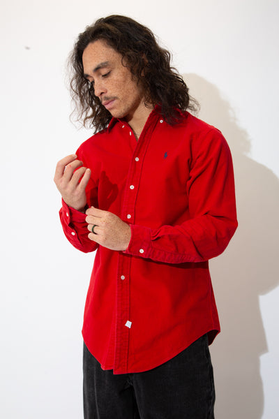 Super soft button-up, red in colour, thick in feel and comfy in fit! With full-length white buttons and a navy blue embroidered Ralph Lauren logo on the left ches